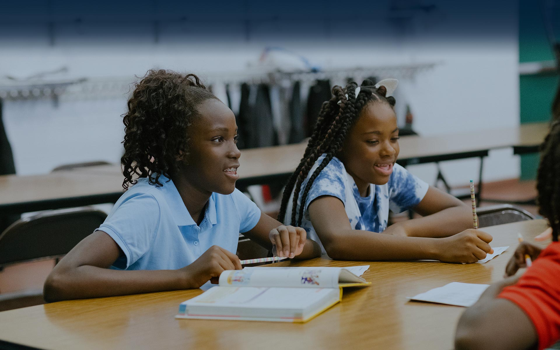 Two young girls smile and work on their schoolwork.