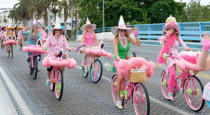 "The ""Witches of Delray"" ride their pink, decorated bicycles over the bridge in Delray Beach."