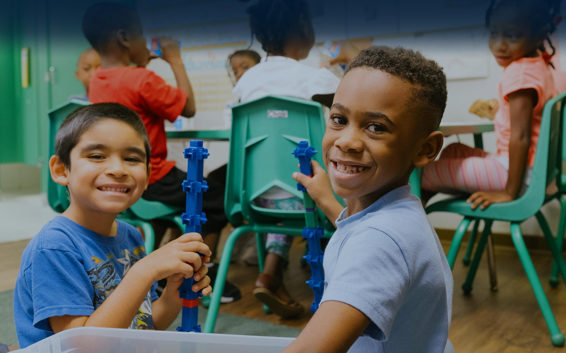 Two young boys smiling and playing with construction toys together.